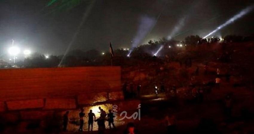 أضواء ليزر وشعلات نار تضيء سماء معركة ضد مستوطنة جديدة بالضفة