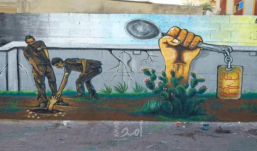 """رسالة شعبٍ رغم الحصار… جدارية في قطاع غزة تجسد """"نفق الحرية"""" - صور"""